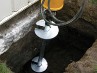 Installing a helical pier system in the earth around a foundation in Fresno